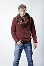 Stylish blond man in sweater scarf and jeans standing on white background Royalty Free Stock Photo