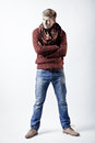 Stylish blond man in sweater scarf and jeans standing on white background Royalty Free Stock Images