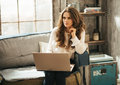 Stylish brunet woman sitting on couch and working on laptop computer in loft designed room Royalty Free Stock Image