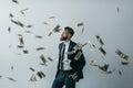 Stylish businessman with falling dollar banknotes on grey Royalty Free Stock Photo