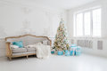 Stylish Christmas interior with an elegant sofa. Comfort home. Presents gifts underneath the tree in living room Royalty Free Stock Photo