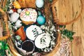 Stylish Easter eggs, easter bread cake, ham, beets, sausage, butter, green branches in wicker basket on rustic fabric with spring Royalty Free Stock Photo