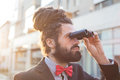 Stylish elegant dreadlocks businessman binoculars in business landscape Royalty Free Stock Photos