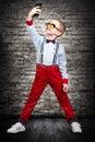 Stylish fashion boy making selfie on mobile phone, portrait.Kid`s fashion. Royalty Free Stock Photo
