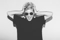 Stylish fashion sexy blonde bad crazy girl in a black t-shirt and rock sunglasses scream holding her head. Dangerous Royalty Free Stock Photo