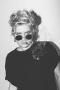Stylish fashion sexy blonde bad girl in a black t-shirt and rock sunglasses covered with cigarette smoke. Dangerous Royalty Free Stock Photo