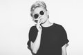 Stylish fashion sexy blonde bad girl in a black t-shirt and rock sunglasses. Dangerous rocky emotional woman smokes Royalty Free Stock Photo