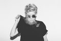 Stylish fashion sexy blonde bad girl in a black t-shirt and rock sunglasses. Dangerous rocky emotional woman. white Royalty Free Stock Photo