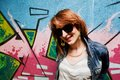 Stylish fashionable girl in jeans jacket portrait against colorful graffiti wall fashion trends subculture Stock Photography