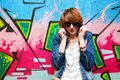 Stylish fashionable girl in jeans jacket portrait against colorful graffiti wall fashion trends subculture Stock Images