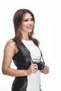 Stylish female photographer beautiful with a shapely figure and friendly smile standing sideways holding her camera in her hands Royalty Free Stock Photo