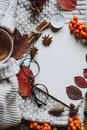 Stylish Flat lay view of autumn leaves and textured scarf on wooden background with cup . Autumn or Winter concept.