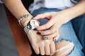 Stylish girl sitting in torn jeans and green modern manicure, bridge silver watch, bracelet. Fashion, lifestyle, beauty, apparel. Royalty Free Stock Photo