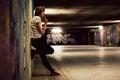 Stylish girl standing in grunge graffiti tunnel, shanty town Royalty Free Stock Photo
