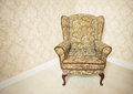 Stylish gold vintage armchair empty upholstered standing in the corner of a room with wallpapered walls in a matching Royalty Free Stock Photo