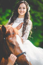 Stylish gorgeous happy brunette bride riding a horse on the back Royalty Free Stock Photo