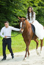 Stylish gorgeous happy brunette bride riding a horse and elegant Royalty Free Stock Photo