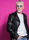 Stylish handsome senior man in leather jacket and sunglasses posing with hand in pocket Royalty Free Stock Photo