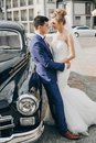 Stylish happy bride and groom posing at old retro car. Gorgeous wedding couple of newlyweds smiling and hugging after wedding Royalty Free Stock Photo