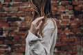 Stylish hipster gypsy woman posing in knitted sweater on backgro Royalty Free Stock Photo