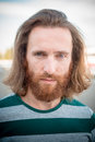Stylish hipster model with long red hair and beard lifestyle in the street Royalty Free Stock Photo