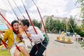 Stylish hipster newlyweds kissing while riding on high carousel in amusement park. Expressive wedding couple at carnival Royalty Free Stock Photo