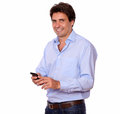 Stylish hispanic man texting on cellphone portrait of a while standing white background Royalty Free Stock Images