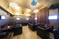 Stylish karaoke bar with leather armchairs and screens Royalty Free Stock Photography
