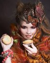 Stylish lady with cake young artistic make up and autumn leafs in her hair and Royalty Free Stock Image