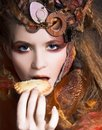 Stylish lady with cake young artistic make up and autumn leafs in her hair and Royalty Free Stock Photography