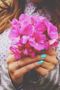 Stylish lady holding bunch of pink flowers in her hands Royalty Free Stock Photo