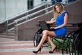 Stylish lady with laptop sitting on a bench Royalty Free Stock Image
