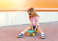 Stylish little girl child with skateboard wearing sunglasses in city Royalty Free Stock Photo