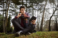 Stylish male student holding notebook and thinking. Sitting on grass in park Royalty Free Stock Photo