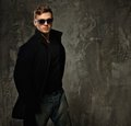 Stylish man in black coat young and sunglasses Royalty Free Stock Image