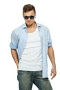 Stylish man in blue shirt and jeans wearing sunglasses isolated on white Royalty Free Stock Images