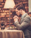 Stylish man pray before meal at restaurant. Royalty Free Stock Photo