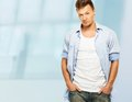 Stylish man in shirt blue and jeans with earring on blue background Stock Photo