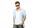 Stylish man in shirt blue and jeans wearing sunglasses isolated on white Royalty Free Stock Photos
