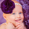 Stylish newborn girl closeup portrait of happy wearing fashionable purple head decoration baby fashion lifestyle joy and fun Stock Photos