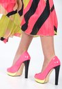 Stylish pink high heels with a green yellow trim partial image of woman s legs and Stock Photos