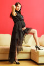 Stylish pregnant woman in black pretty girl evening dress preparing for event glamour look prospective mothering concept Stock Image