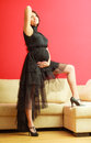 Stylish pregnant woman in black pretty girl evening dress preparing for event glamour look prospective mothering concept Royalty Free Stock Images