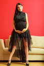 Stylish pregnant woman in black pretty girl evening dress preparing for event prospective mothering concept Stock Photography