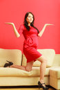 Stylish pregnant woman in red pretty girl dress at home with open hands palm prospective mothering concept Stock Photos