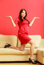 Stylish pregnant woman in red pretty girl dress at home with open hands palm prospective mothering concept Stock Photography