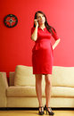 Stylish pregnant woman in red pretty girl dress talking on cellular phone at home prospective mothering using technology concept Royalty Free Stock Photography