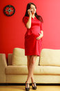Stylish pregnant woman in red pretty girl dress talking on cellular phone at home prospective mothering using technology concept Stock Photos