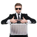 Stylish security guard holds metal suitcase. Royalty Free Stock Photo