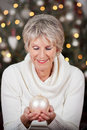 Stylish senior lady with a christmas bauble beautiful smile holding white cupped in her hands in front of sparkling Stock Photos
